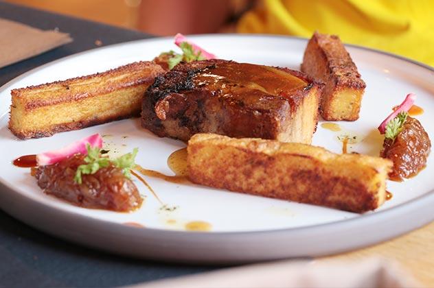 Poitrine de porc marinée puis grillée, confit d'échalotes au miel, frites de polenta à la sarriette
